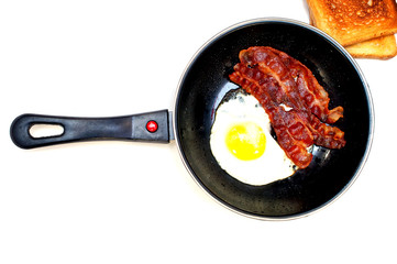 bacon and eggs in a frying pan