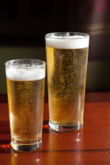 Two glasses of beer on the wooden table