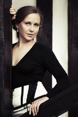 Beautiful fashion woman standing at the wall