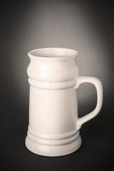 Empty beer mug on grey background