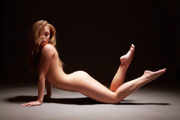 Studio photo of harmonous girl posing nude
