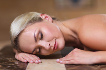 young woman lying on hammam table in turkish bath