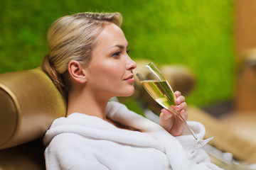 beautiful young woman drinking champagne at spa