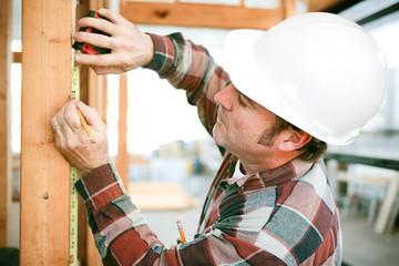 Carpenter Uses Measuring Tape