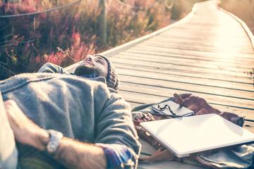 urban man lying on a catwalk in the field enjoying nature