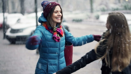 Young girlfriends meeting in the city in winter