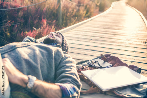 Leinwanddruck Bild urban man lying on a catwalk in the field enjoying nature