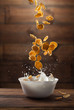 Falling corn flakes with milk splash on wood - 77093029