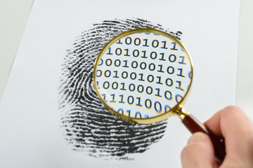 Hand With Magnifying Glass Over A Finger Print