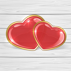 Two shiny hearts on wooden background