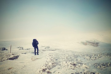 Alone tourist with big backpack and snowshoes walk on snowy path