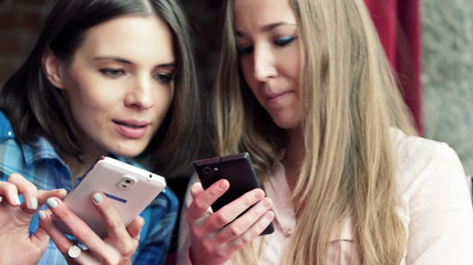 Young girlfriends chatting over smartphone in cafe