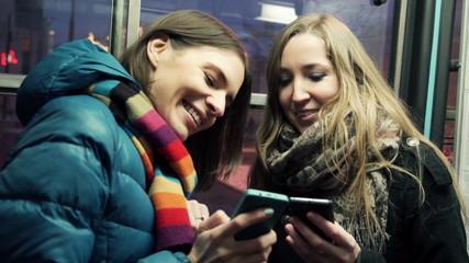 Girlfriends watching funny media on smartphone in tram