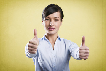 Attractive successful businesswoman giving thumbs up.
