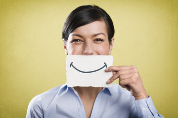 Laughing businesswoman holding white card in front of mouth.