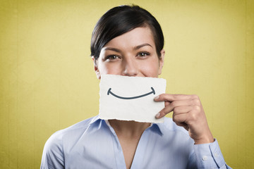 Smiling businesswoman holding blank white card in front of mouth