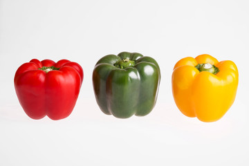 Red, green and yellow pepper on a white background