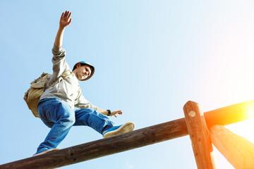 traveler walking balance over wooden construction