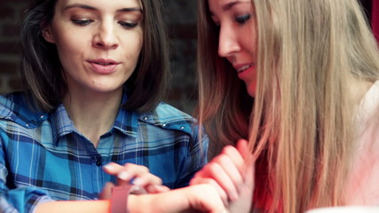 Happy woman showing her new smartwatch gadget to her friend