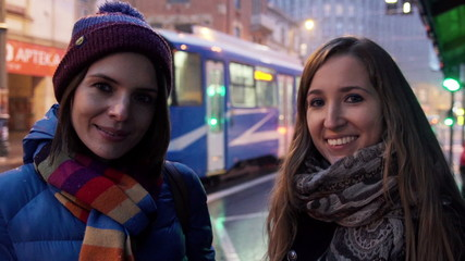 Portrait of two happy beautiful girlfriends in the city