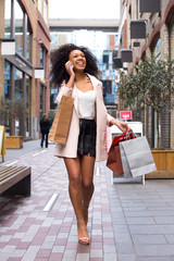 young woman with shopping bags on the phone.