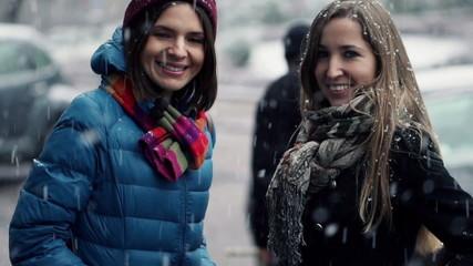 Beautiful happy girlfriends sitting in the city in winter