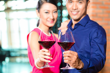 Asian couple with glass of red wine