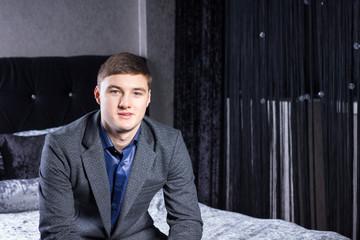 Smiling Young Man in Gray Coat Looking at Camera