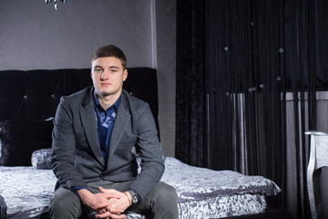 Young Man in Formal Wear Sitting on Bed