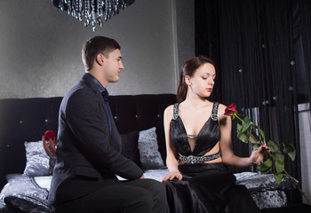 Couple in Elegant Outfits Sitting at the Bedroom
