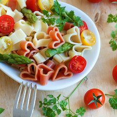 Romantic dinner. Delicious heart-shaped pasta with tomatoes, asp