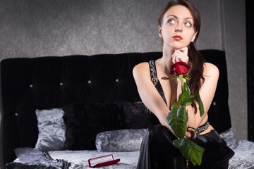 Thoughtful Pretty Woman with Red Rose Flower