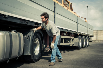 Truck driver working on truck tires
