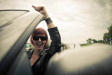Excited woman driving her convertible car