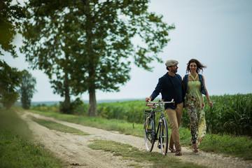 Happy couple walking holding bike.