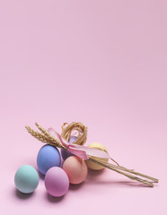 Easter composition of colorful eggs and sheaf of wheat card