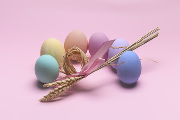 Painted Easter eggs composition with sheaf of wheat