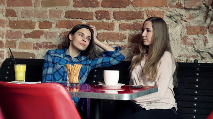 Two young beautiful girlfriends talking in cafe