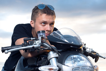 man leaned on the steering wheel of his bike