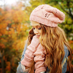 Woman dressed in pink knitted hat and gloves.