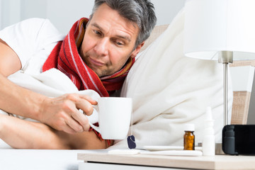 Sick Man Having Coffee In Bed