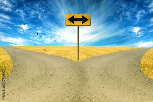 Leinwanddruck Bild two roads, road sign ahead with arrows blue sky background