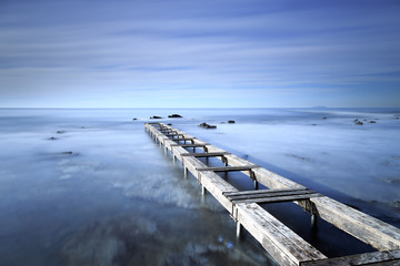 Wooden pier or jetty on a blue ocean in the morning.Long Exposur