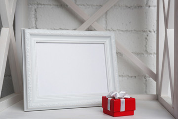 Photo frame with present box on shelf, on brick wall background