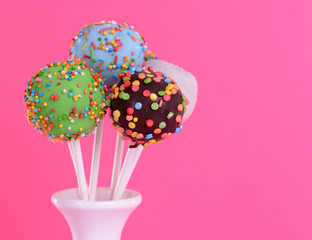 Sweet cake pops in vase on pink background
