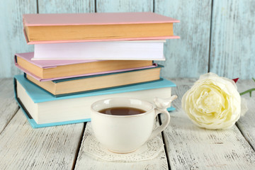 Cup of tea with books on wooden background