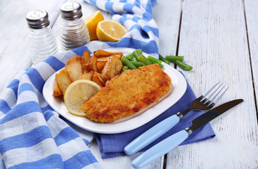 Breaded fried fish fillet and potatoes with asparagus and