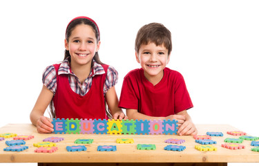 Two kids at the table with puzzle letters