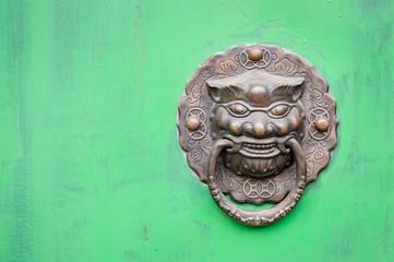 Lion-shaped door knocker against a bright green door, China
