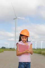 Girl engineer or architect with white safety hat and wind turbin